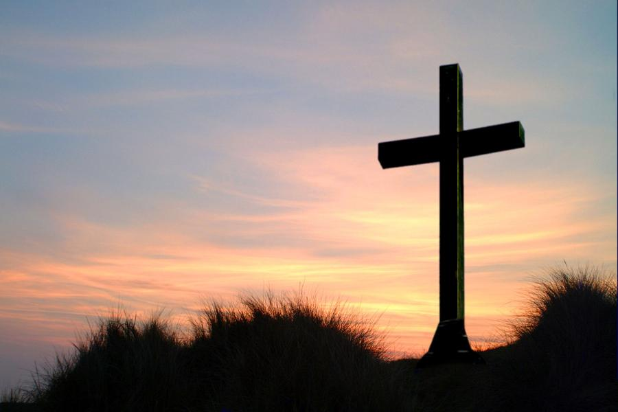 a cross stands on a hill with a sunset in the background