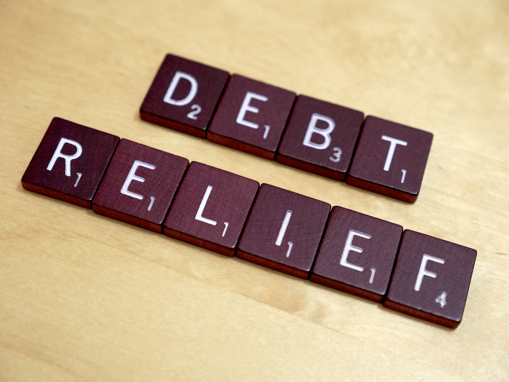 "letters on small tiles that spell out the words ""Debt Relief)"