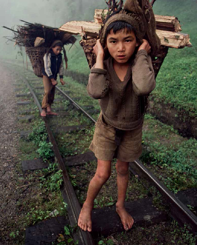 boys carrying logs on train track